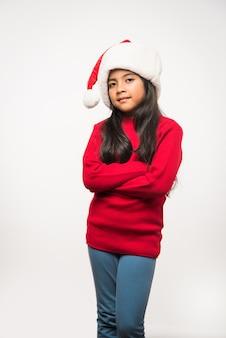 Linda garota indiana asiática com chapéu de papai noel, comemorando o natal em pé, isolada sobre um fundo simples