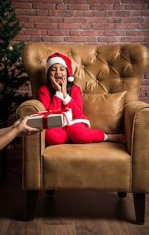 Linda garota indiana asiática comemorando o natal com vestido e chapéu de papai noel, sentada sobre o sofá com presentes e a árvore no fundo contra a parede de tijolo vermelho, iluminação de sonho
