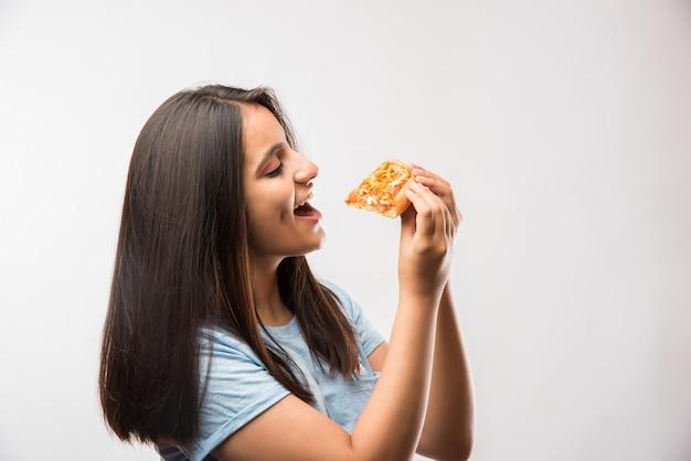 Linda garota indiana asiática comendo uma fatia de pizza em pé, isolada sobre um fundo branco