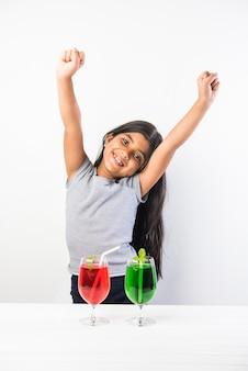 Linda garota indiana asiática posando com uma bebida gelada ou suco fresco na mesa sobre fundo branco