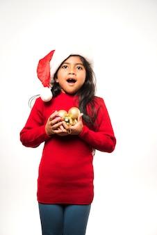 Linda garota indiana asiática segurando um presente de natal isolado sobre um fundo simples