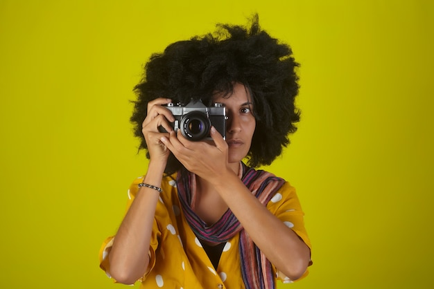 Linda garota indiana com um penteado afro encaracolado falando fotos com a câmera retro na parede amarela