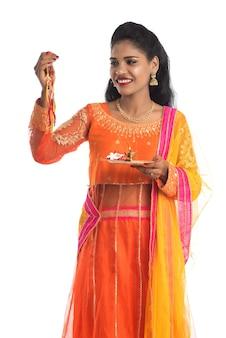 Linda garota indiana mostrando rakhi com pooja thali por ocasião do raksha bandhan.