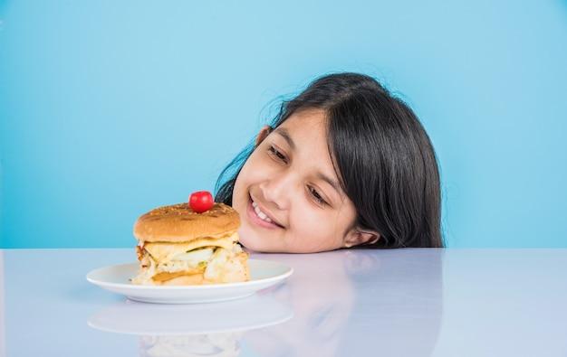 Linda garota indiana ou asiática comendo hambúrguer saboroso, sanduíche ou pizza em um prato ou caixa. permanente isolado sobre fundo azul ou amarelo.