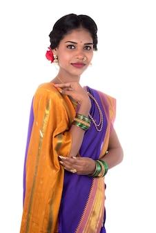 Linda garota indiana posando em tradicional saree indiano em fundo branco.