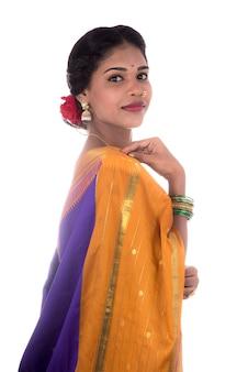 Linda garota indiana posando em tradicional saree indiano na parede branca.