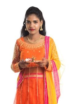 Linda garota indiana segurando pooja thali ou fazendo uma adoração em branco