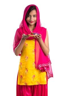 Linda garota indiana segurando pooja thali ou fazendo uma adoração em um branco