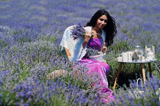 Linda garota indiana usando um vestido tradicional saree da índia sentada em um campo de lavanda roxa
