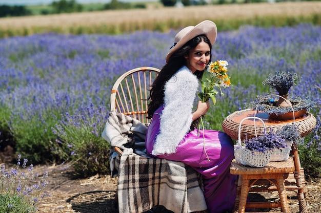 Linda garota indiana usar vestido tradicional saree india em campo de lavanda roxa.