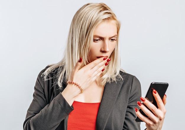 Linda garota infeliz segurando o telefone em um espaço cinza isolado