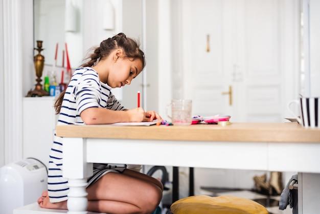 Linda garota inteligente da escola primária, aprendendo a escrever, fazendo a lição de casa, sentada à mesa