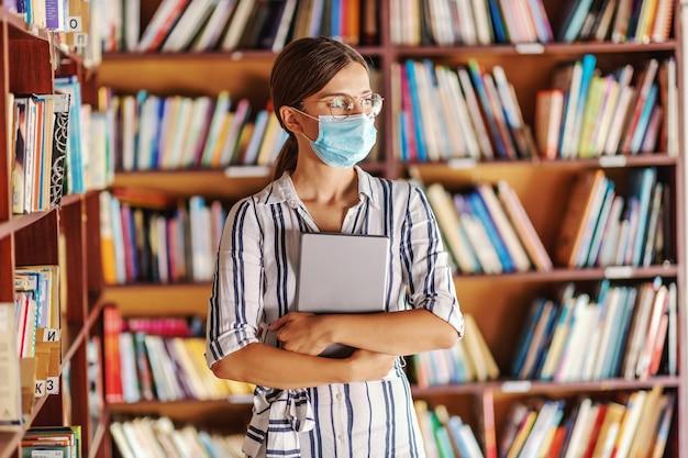 Linda garota inteligente do primeiro ano com máscara facial em pé na biblioteca