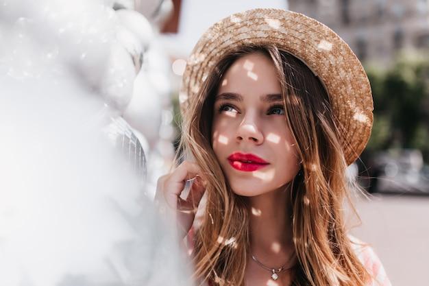 Linda garota interessada em pé nas sombras e olhando para cima. foto ao ar livre de alegre senhora europeia com chapéu de palha.
