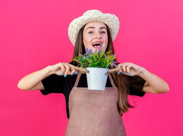 Linda garota jardineira alegre de uniforme, usando chapéu de jardinagem, segurando uma flor em um vaso de flores isolado no fundo rosa