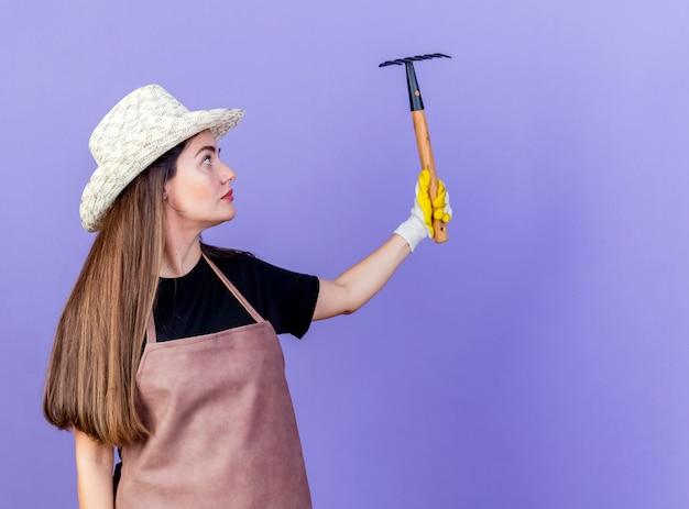 Linda garota jardineira de uniforme usando chapéu de jardinagem e luvas, levantando e olhando para o ancinho isolado em um fundo azul com espaço de cópia