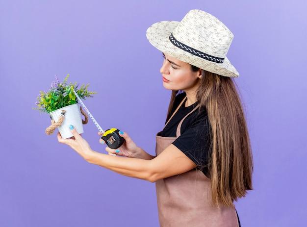 Linda garota jardineira de uniforme, usando um chapéu de jardinagem, medindo a flor em um vaso de flores com fita métrica isolada no fundo azul.