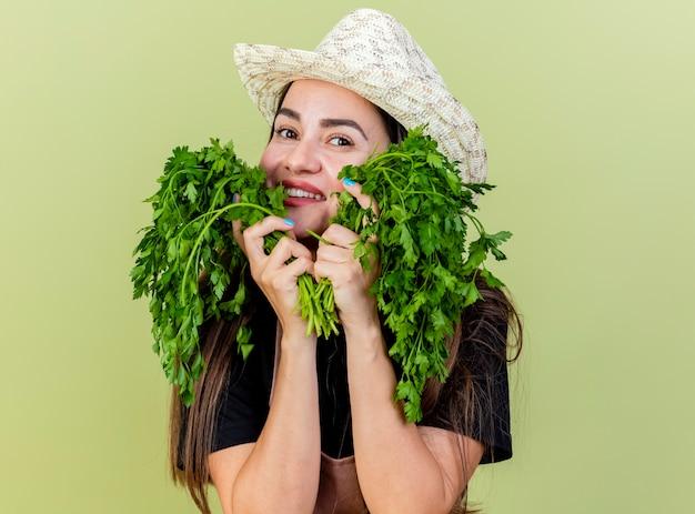 Linda garota jardineira sorridente de uniforme usando chapéu de jardinagem colocando coentro nas bochechas isoladas em fundo verde oliva