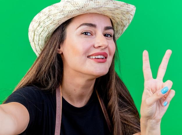 Linda garota jardineira sorridente de uniforme usando chapéu de jardinagem segurando a câmera e mostrando um gesto de paz isolado no verde