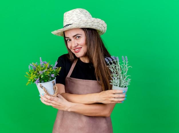 Linda garota jardineira sorridente de uniforme usando chapéu de jardinagem segurando e cruzando flores em um vaso de flores isolado sobre fundo verde