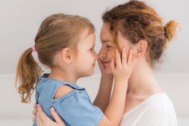 Linda garota jovem abraçando a mãe em casa