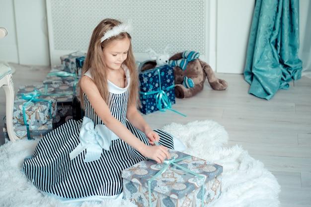 Linda garota jovem abre presentes na sala de decoração de natal. toned