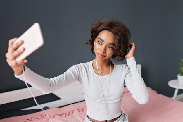 Linda garota jovem, adolescente tomando selfie, ouvindo música na cama com tapete rosa na sala com parede cinza. vestindo camiseta cinza claro com mangas compridas, triângulo pendente.