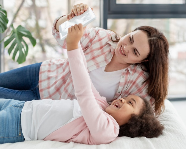 Linda garota jovem assistindo desenhos com a mãe