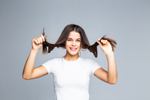 Linda garota jovem brincando com o cabelo dela isolado na cinza