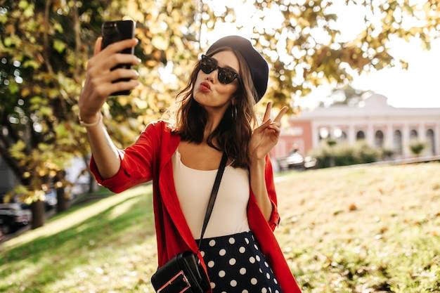Linda garota jovem com cabelo castanho e lábios vermelhos, boina, óculos de sol pretos, blusa e camisa elegantes, fazendo selfie ao ar livre