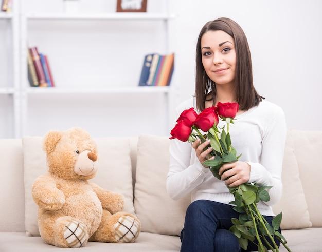 Linda garota jovem com flores em casa.