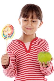 Linda garota jovem com um pirulito e uma maçã sobre fundo branco