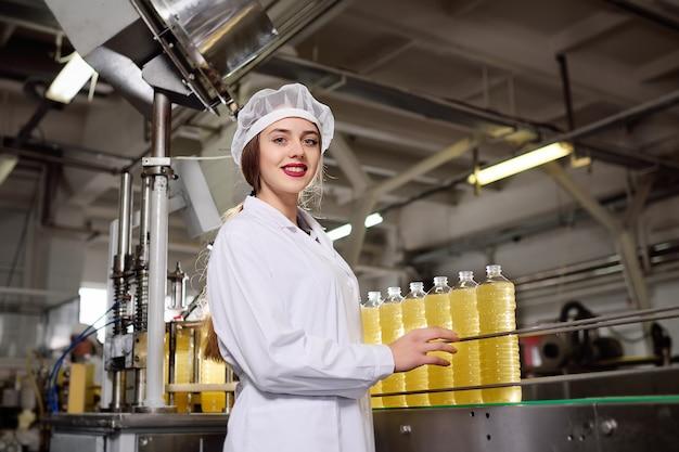 Linda garota jovem com uma garrafa de girassol ou azeite