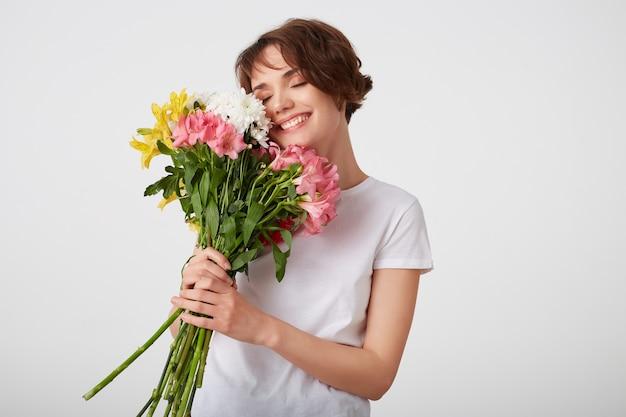Linda garota jovem de cabelos curtos em t-shirt branca em branco, segurando um buquê de flores coloridas, apreciando o cheiro, amplamente sorrindo com os olhos fechados, de pé sobre um fundo branco.