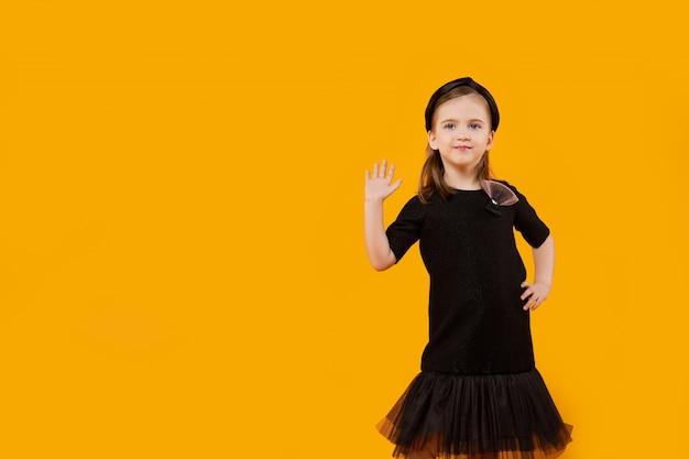 Linda garota jovem em vestido de tule preto retrô e faixa de cabelo mostrando alto gesto cinco