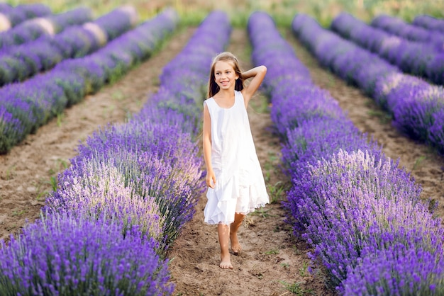 Linda garota jovem entra em um campo de lavanda. ela está usando um vestido de verão branco.