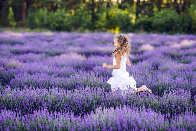 Linda garota jovem está correndo em um campo de lavanda. ela está usando um vestido de verão branco.