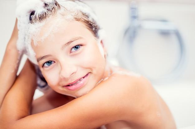 Linda garota jovem no chuveiro, lavando o cabelo e o rosto com shampoo.