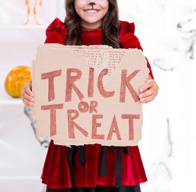 Linda garota jovem segurando placa doce ou travessura