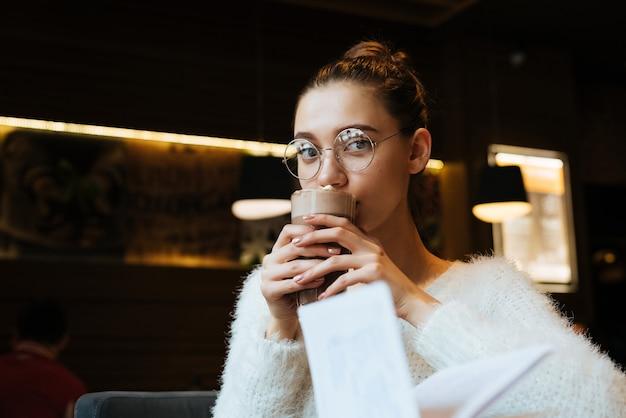 Linda garota jovem usando óculos, sentada em um café, bebendo cappuccino depois da escola