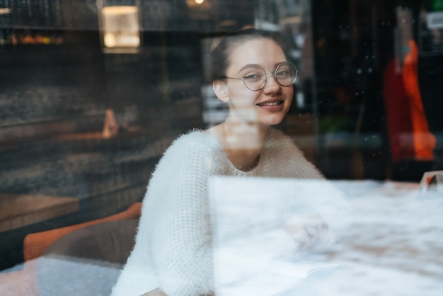 Linda garota jovem usando óculos, sentada no café depois da aula e sorrindo
