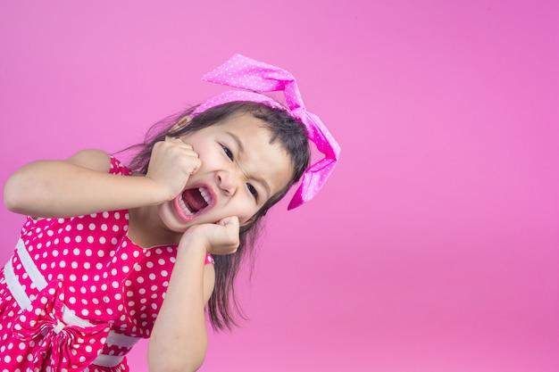 Linda garota jovem vestindo uma camisa listrada vermelha, amarrou um laço rosa na cabeça e rosa.