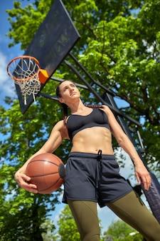 Linda garota latina esportiva com uma bola de basquete sob o ringue em uma quadra de basquete de rua