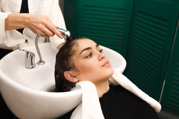 Linda garota lava a cabeça em uma beleza. cabeleireiro está lavando o cabelo para o cliente