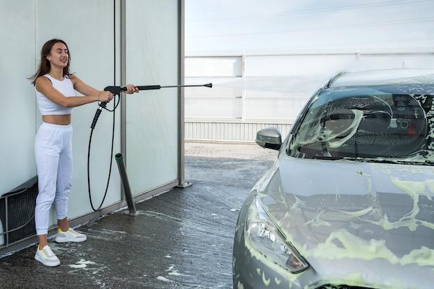 Linda garota lava a espuma com uma pistola d'água de seu carro no posto de lavagem de carros self-service