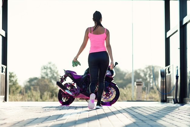 Linda garota lava a motocicleta e enxuga a espuma no lava-jato self-service