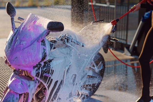 Linda garota lava uma motocicleta no lava-rápido self-service com água em alta pressão