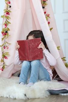 Linda garota lendo um livro sobre decoração fofa