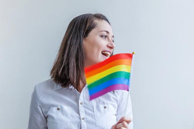 Linda garota lésbica caucasiana com bandeira lgbt arco-íris isolada na parede branca, olhando feliz e animado. retrato de jovem gay pride. direitos iguais para o conceito de comunidade lgbtq.