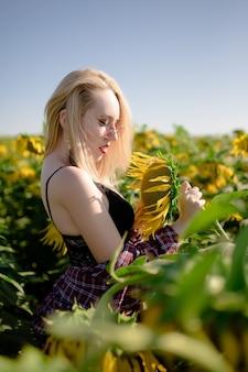 Linda garota linda em lingerie preta em um campo de girassóis, sorrindo com um lindo sorriso
